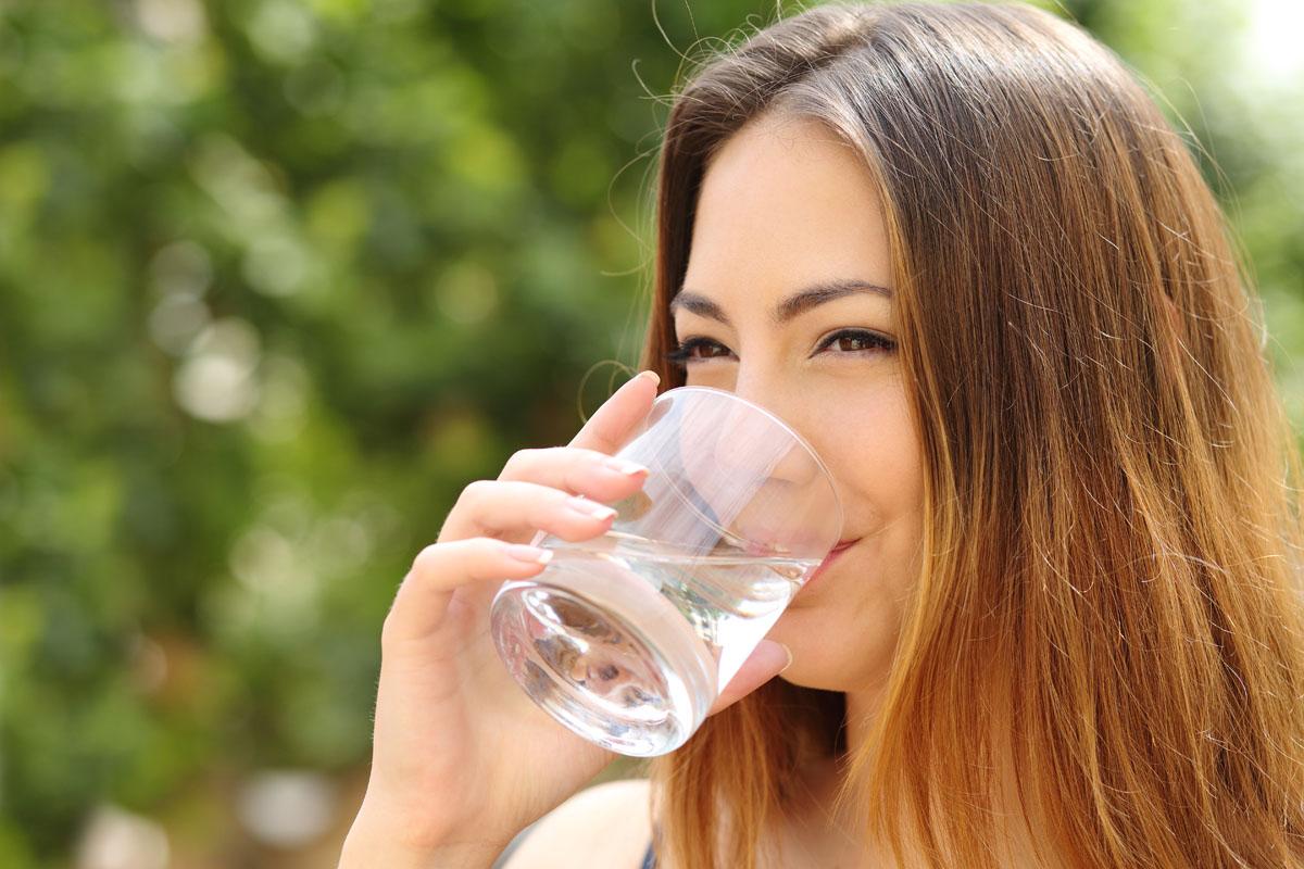 mulher bebendo água para se hidratar