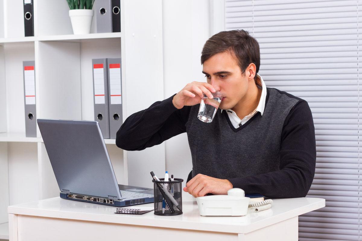 homem bebendo copo de água durante o trabalho