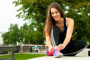 jovem-sentada-em-um-parque-amarrando-o-tenis