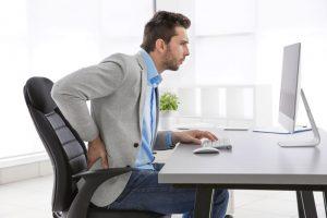 homem-sentado-na-cadeira-do-trabalho-com-as-maos-nas-costas-com-dores-na-coluna-