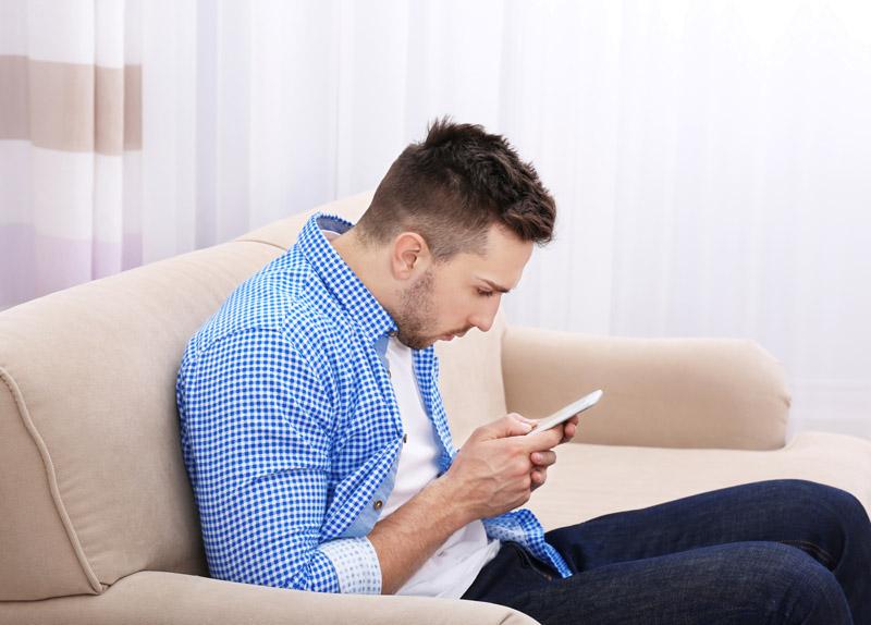 homem-sentado-no-sofa-mexendo-no-celular-com-pescoço-inlinado