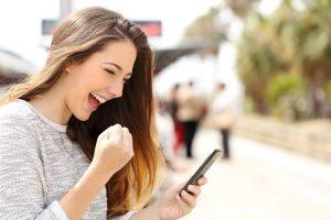 mulher-comemorando-boas-noticias-pelo-celular-saude-mental