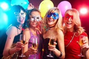 mulheres-com-máscaras-de-carnaval-seguram-taças-de-bebidas