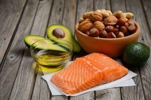 cabacate-nozes-castanhas-no-pote-peixe-exemplos-de-gorduras-do-bem-expostas-na-mesa