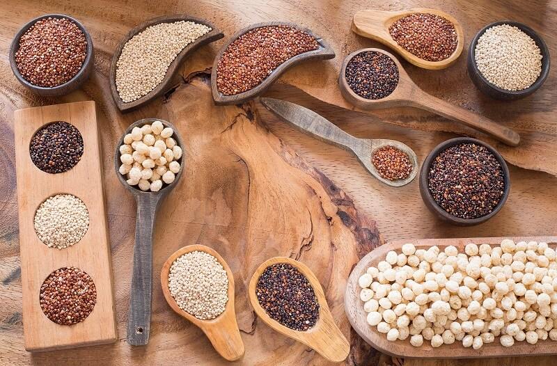 várias-sementes-andinas-dispostas-em-colheres-de-pau-e-recipientes-de-madeira