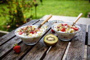 duas-taças-de-iogurte-com-frutas-e-sementes-andinas-postos-numa-mesa-de-madeira