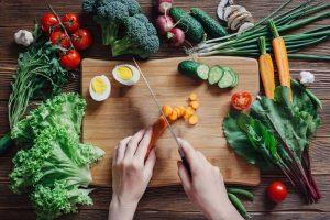 pessoa cortando cenoura e outros legumes e vegetais